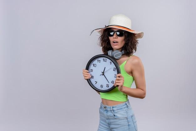 Zaskoczona młoda kobieta z krótkimi włosami w zielonej bluzce w okularach przeciwsłonecznych i kapeluszu przeciwsłonecznym trzyma zegar ścienny na białym tle