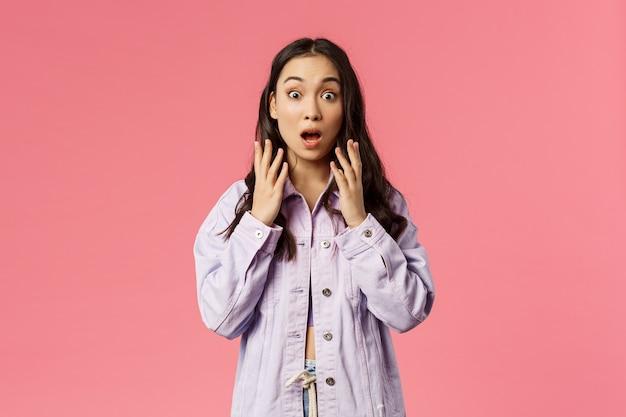Zaskoczona młoda koreańska dziewczyna widząc coś szokującego, wpatrująca się w kamerę z zaskoczeniem, opadająca szczęka i z trudem łapiąc powietrze, trzymaj ręce uniesione zaskoczone nowinami, stoisko