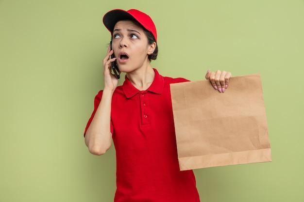 Zaskoczona młoda ładna dostawa kobieta rozmawia przez telefon i trzyma papierowe opakowanie żywności, patrząc na bok