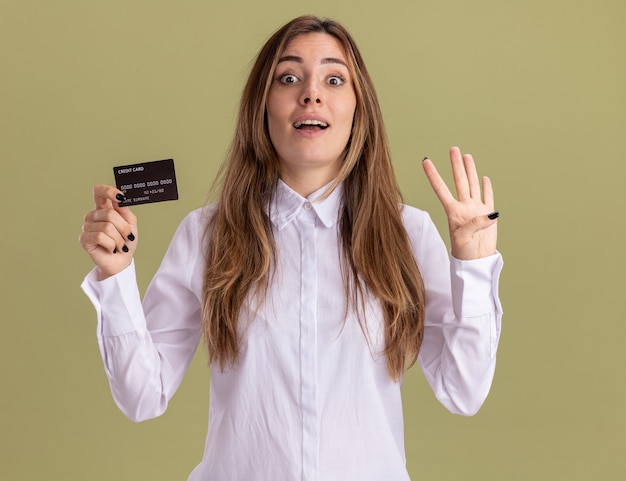 Zaskoczona młoda ładna kaukaska dziewczyna trzyma kartę kredytową i gestykuluje cztery palcami