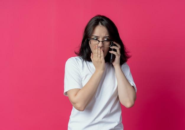 Zaskoczona młoda ładna kaukaska dziewczyna w okularach, patrząc na bok, rozmawiając przez telefon, kładąc dłoń na ustach na białym tle na szkarłatnym tle z miejsca na kopię