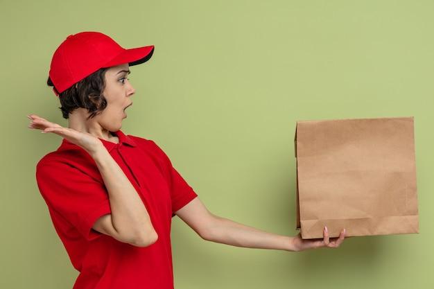 Zaskoczona młoda ładna kobieta dostawy trzymająca i patrząca na papierową torbę na jedzenie stojącą z podniesioną ręką