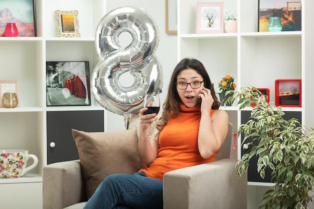 Zaskoczona młoda ładna kobieta w okularach rozmawia przez telefon i trzyma kieliszek wina, siedząc na fotelu w salonie w marcowy dzień kobiet