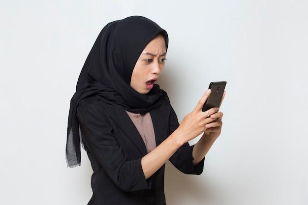 Zaskoczona młoda muzułmańska kobieta z azji używająca telefonu komórkowego na białym tle