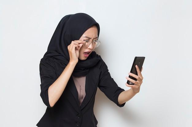 Zaskoczona młoda muzułmańska kobieta z azji w okularach przy użyciu telefonu komórkowego na białym tle