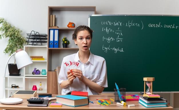 Zaskoczona młoda nauczycielka matematyki siedząca przy biurku z przyborami szkolnymi trzymająca rosyjskie litery alfabetu fani patrzący na przód w klasie