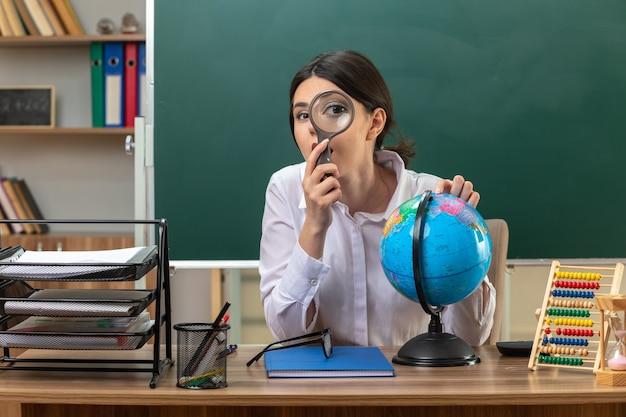 Zaskoczona młoda nauczycielka siedząca przy stole z narzędziami szkolnymi trzymająca kulę ziemską, patrząca z lupą w klasie
