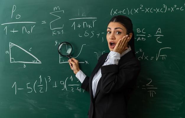 Zaskoczona młoda nauczycielka stojąca przed tablicą, kładąca dłoń na policzku w klasie
