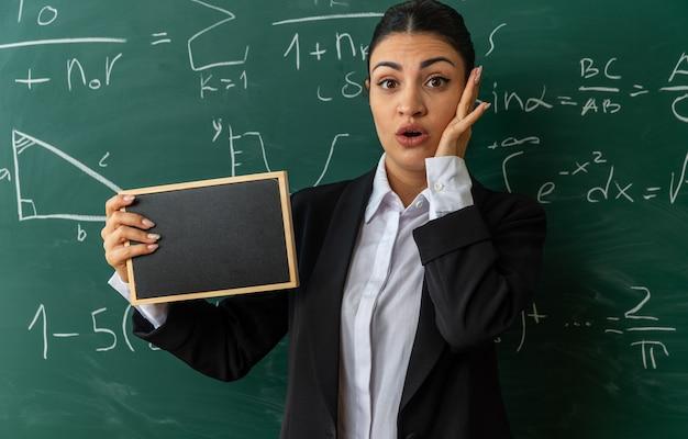 Zaskoczona młoda nauczycielka stojąca przed tablicą trzymająca mini tablicę w klasie