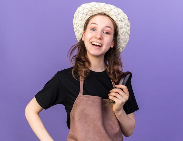 Zaskoczona młoda ogrodniczka w kapeluszu ogrodniczym trzymająca bakłażana