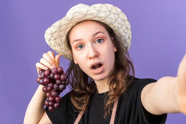 Zaskoczona młoda ogrodniczka w kapeluszu ogrodniczym trzymająca winogrona z aparatem