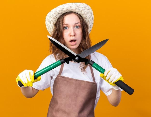 Zaskoczona młoda ogrodniczka w kapeluszu ogrodniczym z rękawiczkami trzymająca sekator na białym tle na pomarańczowej ścianie