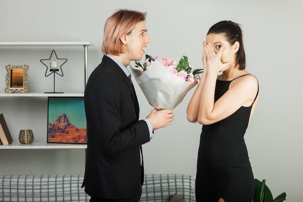 Zaskoczona młoda para przytuliła się na walentynki, a dziewczyna z bukietem szepcze stojąc w salonie