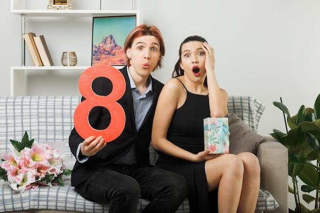 Zaskoczona młoda para w szczęśliwy dzień kobiet trzymająca numer osiem z obecną dziewczyną kładącą rękę na policzku, siedzącą na kanapie w salonie