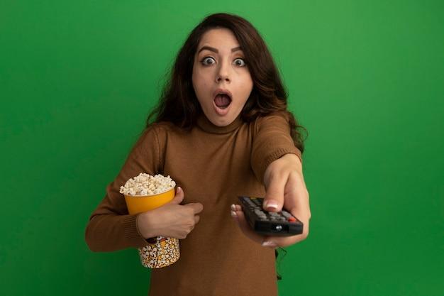 Zaskoczona młoda piękna dziewczyna przytula wiadro popcornu i trzyma pilota od telewizora z przodu na białym tle na zielonej ścianie