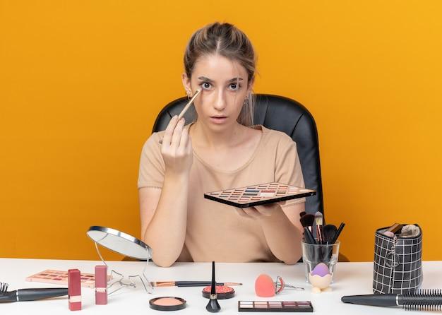 Zaskoczona młoda piękna dziewczyna siedzi przy stole z narzędziami do makijażu, stosując cień do powiek z pędzlem do makijażu na białym tle na pomarańczowym tle