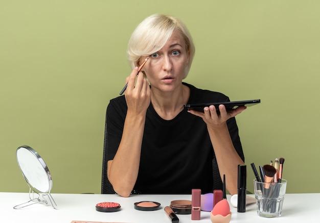 Zaskoczona młoda piękna dziewczyna siedzi przy stole z narzędziami do makijażu, stosując cień do powiek za pomocą pędzla do makijażu na oliwkowozielonym tle