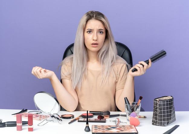 Zaskoczona młoda piękna dziewczyna siedzi przy stole z narzędziami do makijażu trzymając grzebień na białym tle na niebieskim tle
