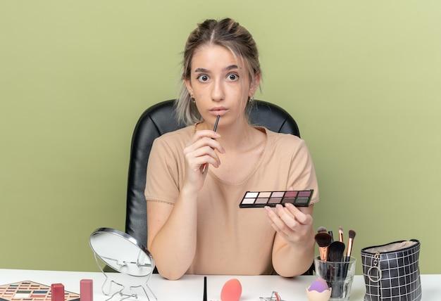 Zaskoczona młoda piękna dziewczyna siedzi przy stole z narzędziami do makijażu, trzymając pędzel z paletą cieni do powiek na oliwkowym tle