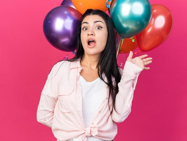 Zaskoczona młoda piękna dziewczyna trzyma balony rozkładające rękę