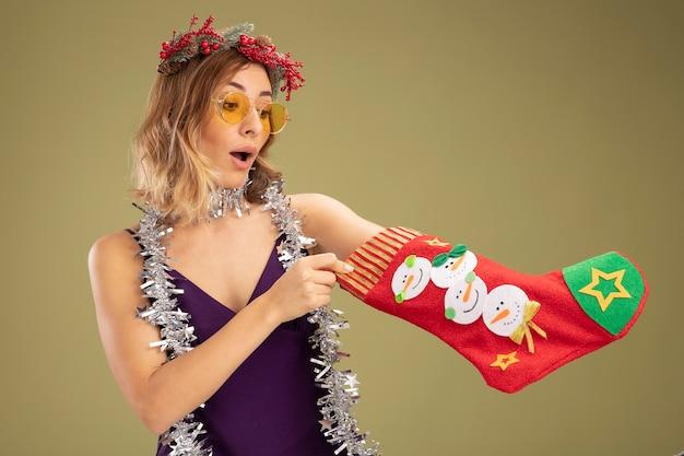 Zaskoczona młoda piękna dziewczyna ubrana w fioletową sukienkę z okularami i wieniec z girlandą na szyi, kładąc rękę w świąteczną skarpetę na białym tle na oliwkowo-zielonym tle