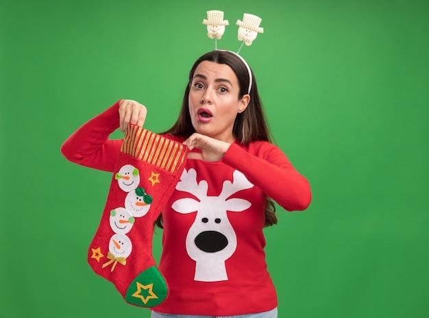 Zaskoczona młoda piękna dziewczyna ubrana w świąteczny sweter z świątecznym obręczem do włosów, trzymając świąteczne skarpetki na białym tle na zielonym tle