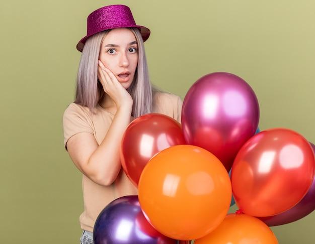 Zaskoczona młoda piękna dziewczyna w imprezowym kapeluszu, stojąca za balonami, kładąc rękę na policzku na oliwkowozielonej ścianie