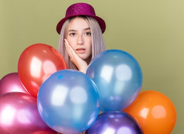 Zaskoczona młoda piękna dziewczyna w imprezowym kapeluszu stojąca za balonami, kładąca dłoń na policzku