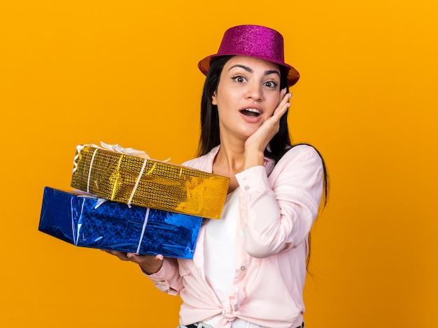 Zaskoczona młoda piękna dziewczyna w imprezowym kapeluszu, trzymająca pudełka z prezentami, kładąc rękę na policzku na pomarańczowej ścianie