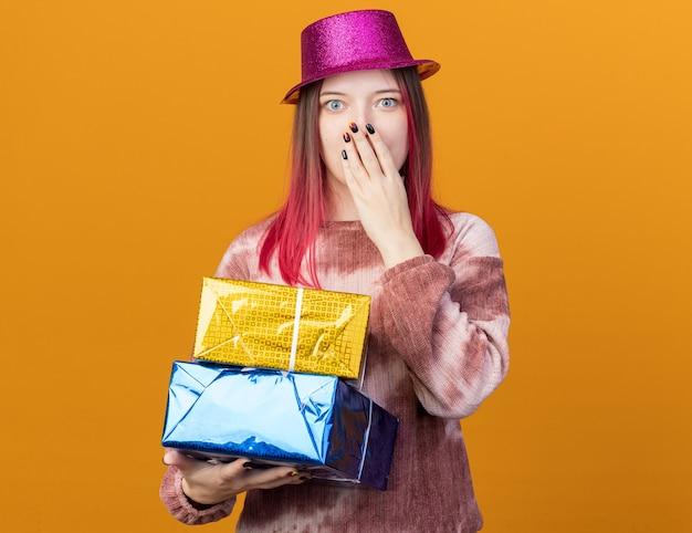 Zaskoczona młoda piękna dziewczyna w imprezowym kapeluszu, trzymająca pudełka z prezentami, zakryła usta dłonią