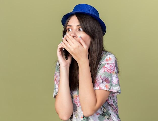 Zaskoczona młoda piękna dziewczyna w kapeluszu imprezowym mówi na ustach zakrytych telefonem ręką odizolowaną na oliwkowozielonej ścianie