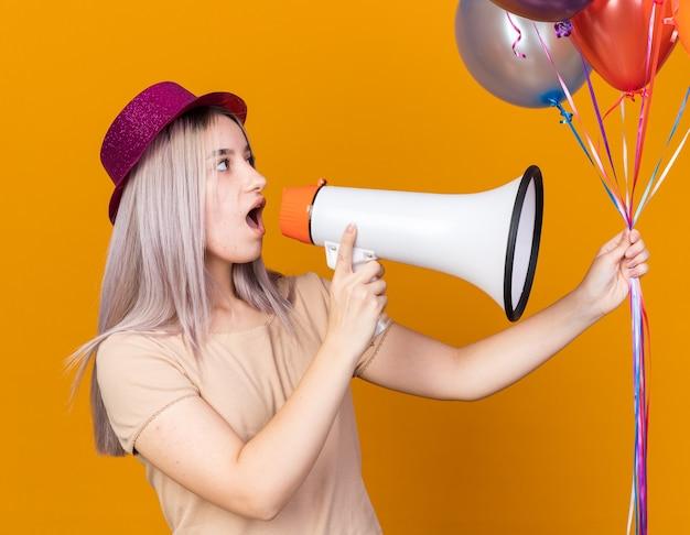 Zaskoczona młoda piękna dziewczyna w kapeluszu imprezowym, trzymająca balony, mówi przez głośnik