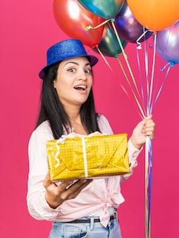 Zaskoczona młoda piękna dziewczyna w kapeluszu imprezowym trzymająca balony z pudełkiem na prezent na różowej ścianie