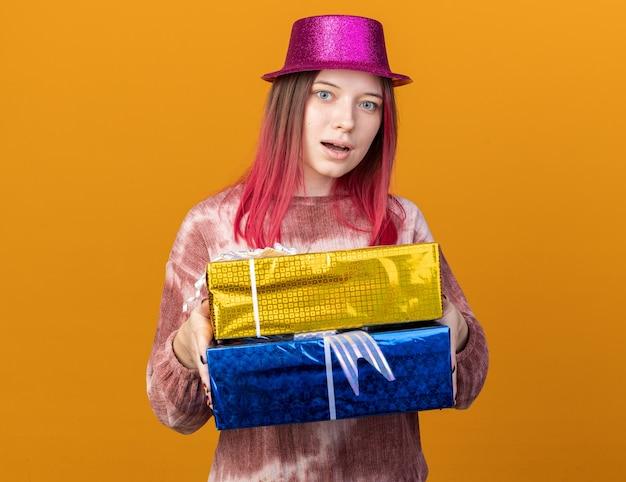 Zaskoczona młoda piękna dziewczyna w kapeluszu imprezowym, trzymająca pudełka na prezenty izolowane na pomarańczowej ścianie