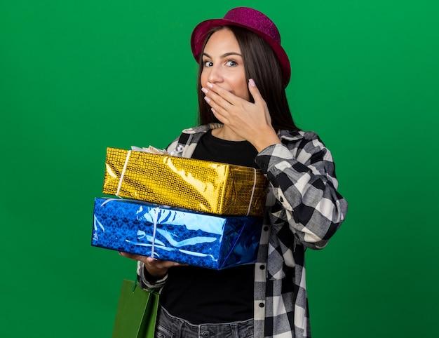 Zaskoczona młoda piękna dziewczyna w kapeluszu imprezowym trzymająca pudełka na prezenty z torbą na prezenty zakrytą ustami ręką odizolowaną na zielonej ścianie