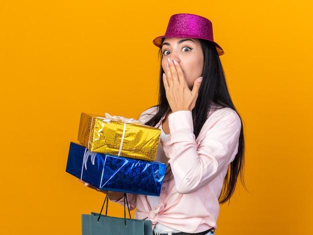 Zaskoczona młoda piękna dziewczyna w kapeluszu imprezowym trzymająca torbę na prezenty z pudełkami na prezenty zakryła usta ręką odizolowaną na pomarańczowej ścianie