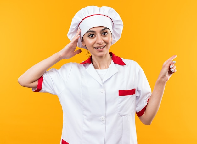 Zaskoczona młoda piękna dziewczyna w mundurze szefa kuchni wskazuje z boku