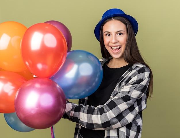 Zaskoczona młoda piękna dziewczyna w niebieskim kapeluszu, trzymając balony