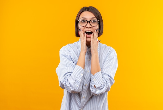 Zaskoczona młoda piękna dziewczyna w okularach, kładąca ręce na policzku na pomarańczowej ścianie