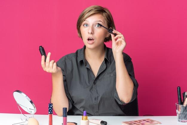 Zaskoczona młoda piękna kobieta siedzi przy stole z narzędziami do makijażu, nakładającymi tusz do rzęs