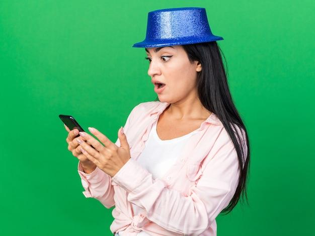 Zaskoczona młoda piękna kobieta w kapeluszu imprezowym trzymająca i patrząca na telefon odizolowany na zielonej ścianie