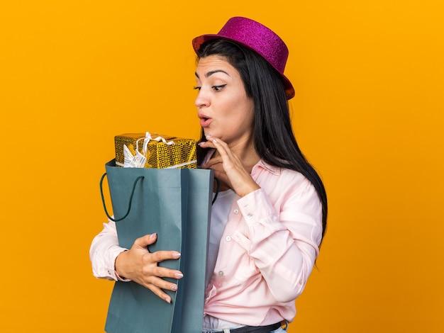 Zaskoczona młoda piękna kobieta w kapeluszu imprezowym, trzymająca i patrząca na torbę z prezentami odizolowaną na pomarańczowej ścianie