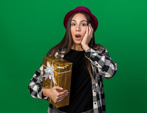 Zaskoczona młoda piękna kobieta w kapeluszu imprezowym, trzymająca pudełko, kładąc rękę na policzku na zielonej ścianie