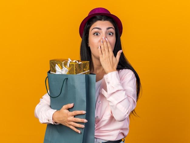 Zaskoczona młoda piękna kobieta w kapeluszu imprezowym trzymająca torbę z prezentami zakrytą ustami ręką odizolowaną na pomarańczowej ścianie