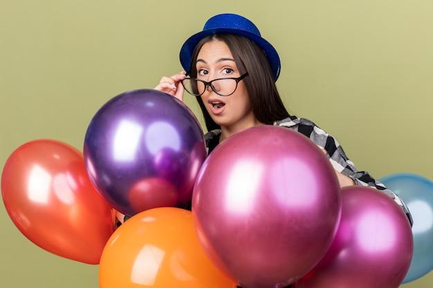 Zaskoczona młoda piękna kobieta w niebieskim kapeluszu w okularach, stojąca za balonami na oliwkowozielonej ścianie