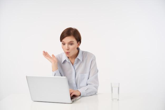 Zaskoczona młoda śliczna, krótkowłosa brunetka kobieta siedzi przy stole na białym tle z nowoczesnym laptopem i patrzy na ekran z szeroko otwartymi oczami, ubrana w formalne ubrania