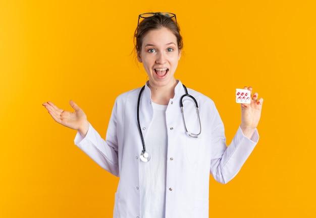 Zaskoczona młoda słowiańska dziewczyna w mundurze lekarza ze stetoskopem trzymająca opakowanie blistrowe z lekarstwem na pomarańczowej ścianie z miejscem na kopię