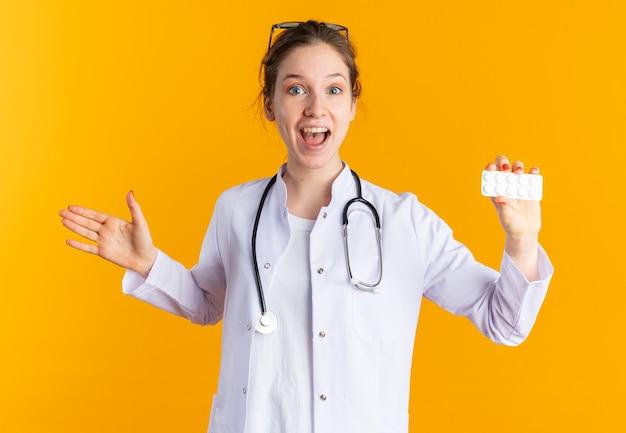 Zaskoczona młoda słowiańska dziewczyna w mundurze lekarza ze stetoskopem trzymająca opakowanie blistrowe z lekiem i trzymająca rękę otwartą na białym tle na pomarańczowej ścianie z miejscem na kopię