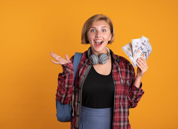 Zaskoczona młoda słowiańska studentka ze słuchawkami w plecaku trzyma rękę otwartą i trzyma pieniądze