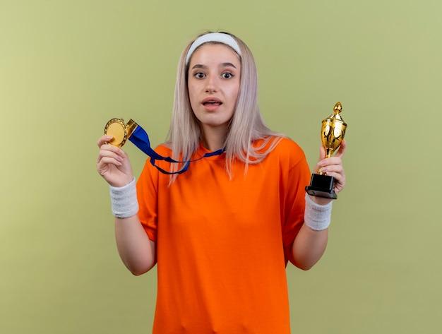 Zaskoczona młoda sportowa dziewczyna rasy kaukaskiej z szelkami w opasce i opaskach na nadgarstku trzyma złoty medal i puchar zwycięzcy